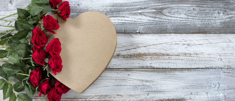 Happy Valentines Day with red roses on top of a heart shaped gift box with  white rustic wooden background