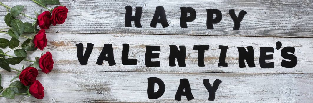 Happy Valentines Day with lovely red roses and large text letters on white rustic wooden background