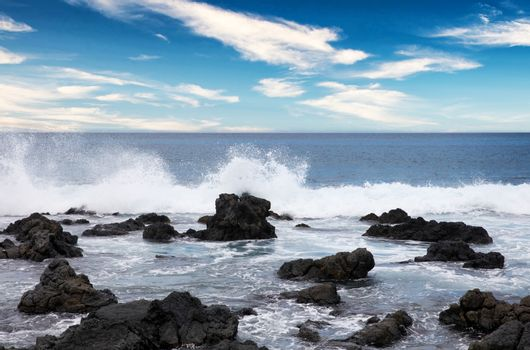 Ocean and rocks with blue sky during daytime