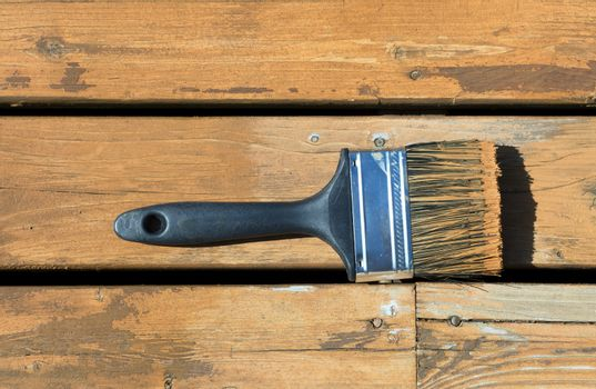 Used paintbrush filled with wood stain on a natural cedar deck