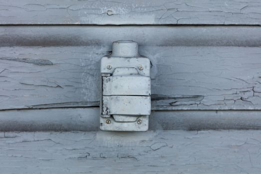 Old electrical outlet box with lead paint peeling off of wood sl