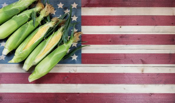 Fresh sweet corn with rustic wooden flag of United States of America