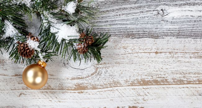 Christmas gold ornament hanging from snowy rough fir tree branch