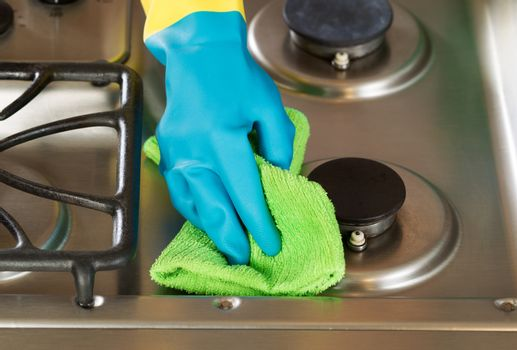 Gloved hand wiping down stove top range with green microfiber ra