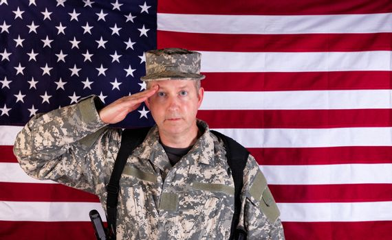 Male veteran solider saluting with USA flag in background while