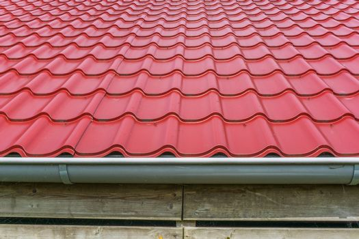 red glossy rooftop tiling with drainpipe