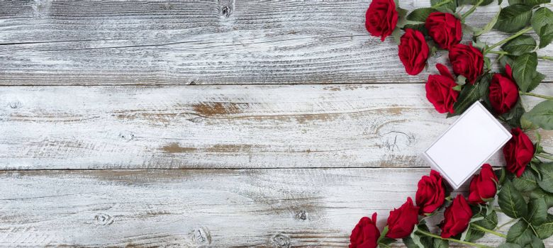 Small gift box with a dozen red roses for Valentines Day on white rustic wood