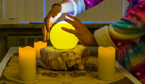 person moving hands around a lighted fortune teller sphere, traditional globe for spirituality and witchcraft