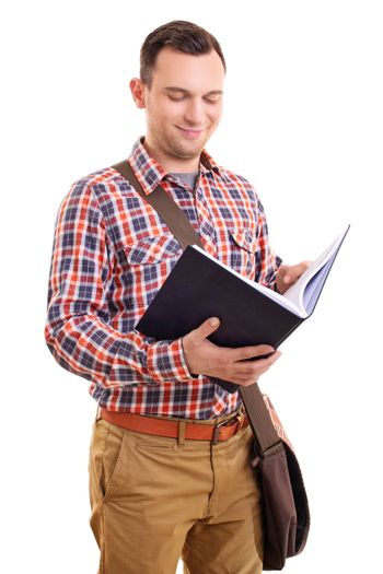 Portrait of a smiling young male student in stylish plaid shirt outfit with a shoulder bag holding and looking at an open notebook, isolated on white background.