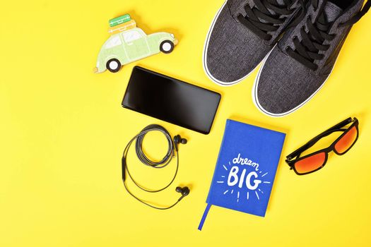 Travel planning, vacation and tourism concept. Top view of traveler's essential accessories including sneakers, sunglasses, smartphone, earphones and a Dream Big notepad on yellow background. Flat lay, copy space.