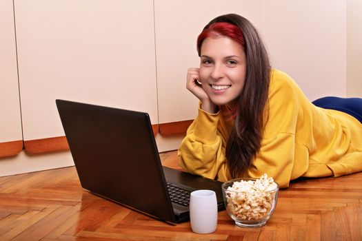 Beautiful smiling young girl in casual clothes lying on the floor of her bedroom, ready to watch a movie on her laptop with a bowl of popcorn and a cup of coffee or tea. Leisure concept.