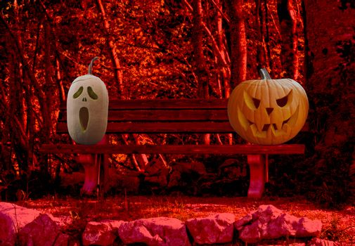Halloween celebration two scary and spooky carved pumpkins on a park bench in a horror forest landscape