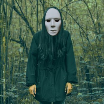 Halloween scary masked women in a creepy forest landscape