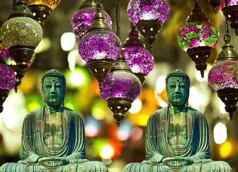 two buddhist statues meditating with lamps and background buddhism card