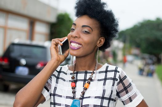 Portrait of pretty African woman in communication in the street with a beautiful smile