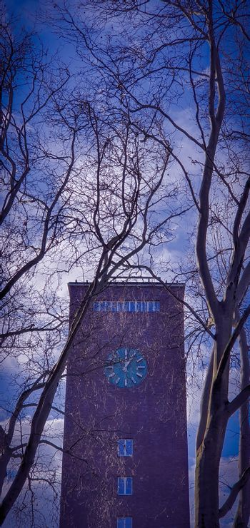 Red brick clock tower against clear blue sky and white clouds, seen through tree branches. Clock tower of the central train station in Oberhausen, Germany.