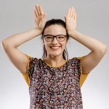 Funny portrait of woman making rabbit ears