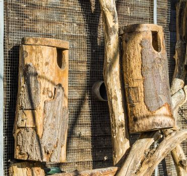 big hand crafted empty wooden bird houses made of a tree trunk and wood hanging on the wall
