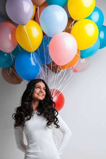 Young pretty woman in white dress with color balloons on white background with copy space for text