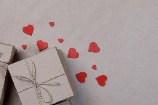 Box with gifts wrapped in brown craft paper and red paper hearts Valentines day concept
