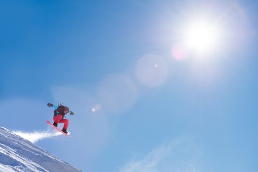Snowboarder Jumping on the Red Snowboard in the Mountains in Bright Rays of Sun. Freeride Snowboarding and Extreme Winter Sports
