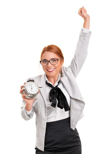 Saving time concept. Success concept. Beautiful excited young businesswoman in a suit holding an old fashioned alarm clock with the other arm raised in celebration, isolated on white background.