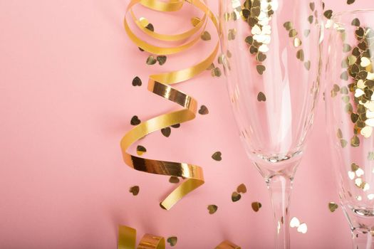 Valentines day champagne flute glasses and heart shaped gold glitters on pink background with copy space for text