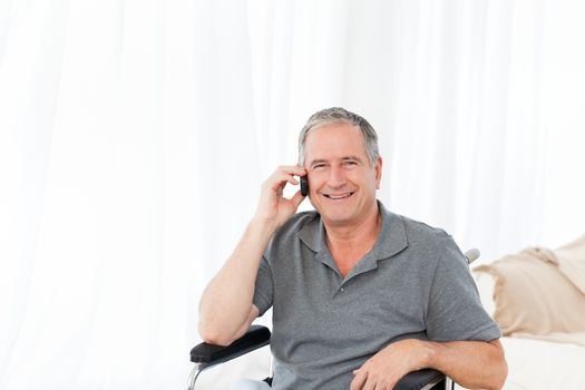 Senior in his wheelchair phoning