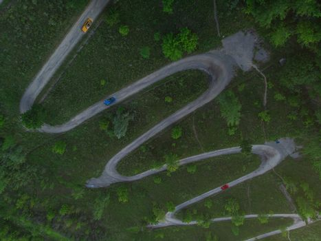 Aerial top vew of winding road in the city, with cars , drone shot