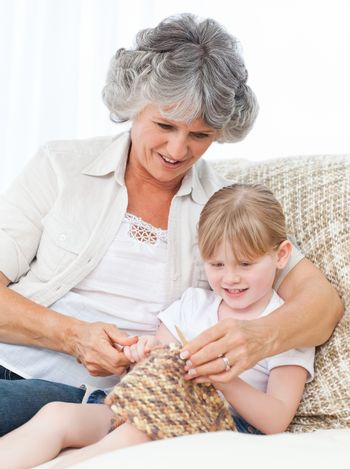 Grandmother helping her granddaughterl to knit