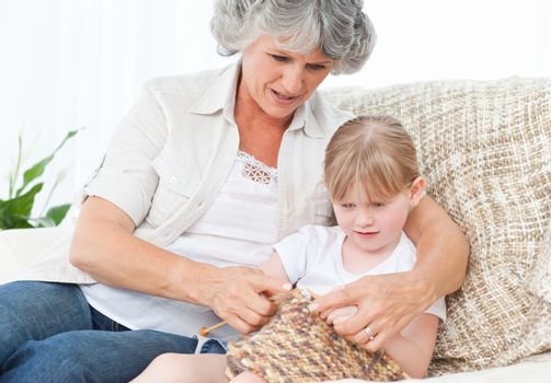 Grandmother helping her little girl to knit