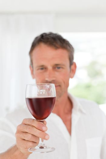 Man with his wineglass in his kitchen