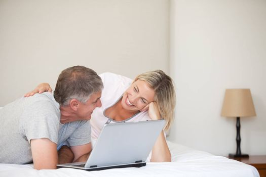 Lovely couple looking at their laptop at home