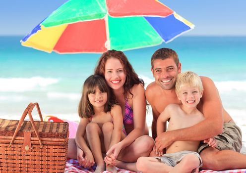 Family posing under a beach umbrella on the beach