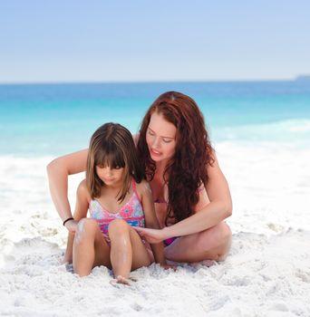 Mother applying sun cream on her daughter