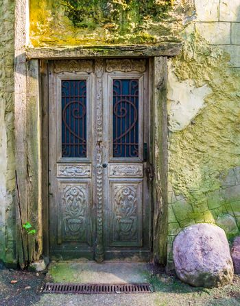 old antique wooden door in a wooden framework with a smooth stone wall outdoor architecture
