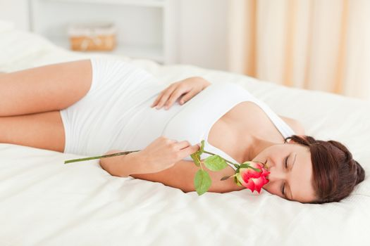Woman with a rose having eyes closed