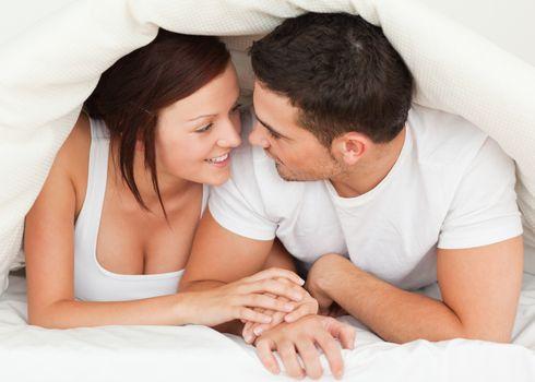 Couple hiding under a blanket