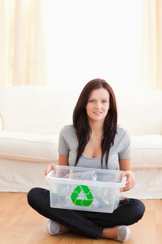 Sitting woman holding recycling bin
