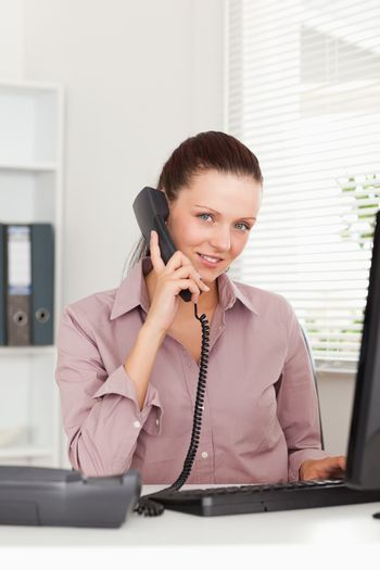 Businesswoman telephoning at workplace