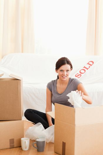 Charming redheaded woman packing her property