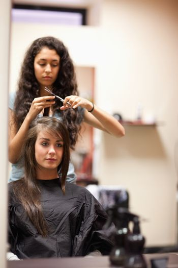 Portrait of a young woman having a haircut