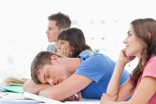 Four students in class as three pay attention one male student sleeps
