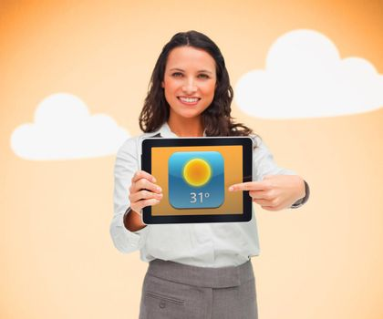 Businesswoman pointing to weather app symbol on tablet on orange cloud background