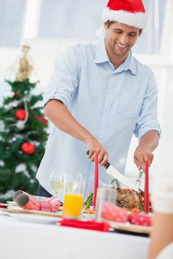 Handsome man wearing a santa hat and carving roast chicken at a christmas dinner