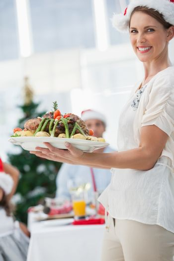 Attractive woman bringing roast chicken at a christmas dinner and looking at camera