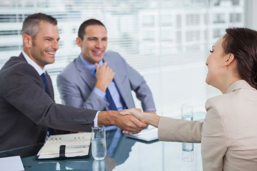 Cheerful young woman shaking hands with her future employer