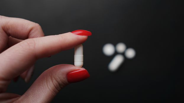 Woman holding pill, capsule in doctor hand close-up. Epidemic and virus concept