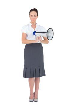 Unsmiling businesswoman holding megaphone