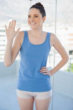 Smiling slender woman in sportswear waving